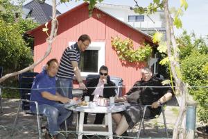 Die Hobbygärtner machen eine Pause und sitzen vor ihrem Gartenhäuschen.