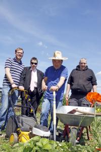 Drei Männer und eine Frau stehen mit Rasenmäher und Schubkarre in ihrem Garten.