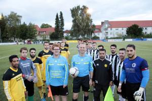 Gruppenbild: Beide Mannschaften und die Schiedsrichter
