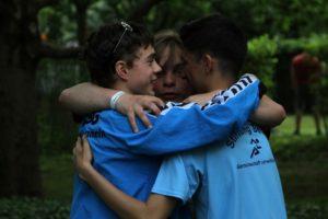 Drei Jungs umarmen sich nach dem Staffel-Lauf